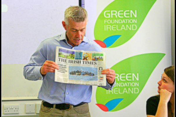 green-foundation-ireland-man-holding-newspaper-article